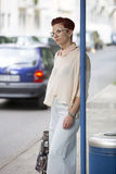 Woman standing at bus stop and waiting Stock Images