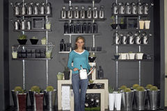 Woman standing beside cacti display in shop, holding watering can, smiling, front view, portrait Royalty Free Stock Photos