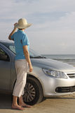 Woman standing beside a car on a beach stock photo
