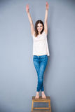 Woman standing on the chair with raised hands up. Happy young woman standing on the chair with raised hands up Royalty Free Stock Image