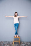Woman standing on the chair Royalty Free Stock Photos