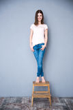 Woman standing on the chair Stock Photography