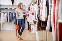 Woman standing and choosing clothes in clothing store. Beautiful young woman standing and choosing clothes in clothing store Stock Photos