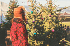 Woman standing by christmas tree outside Stock Photo