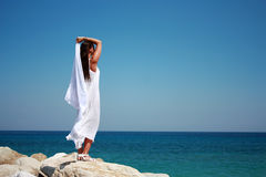 Woman standing on a cliff in a long white dress Royalty Free Stock Photos