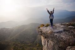 Woman standing on cliff with outstretched arms Stock Photo