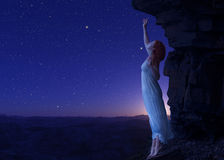 Woman standing on cliff's edge of another planet. Royalty Free Stock Image