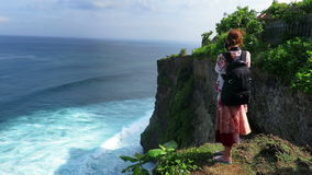 Woman standing on cliff's edge in Uluwatu and taking photos stock video