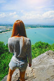 Woman standing on the cliff and see something on the blue sky, blue sea and cloud.  stock photography