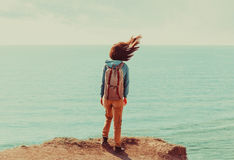 Woman standing on coastline in windy weather. Traveler young woman with backpack standing on coastline near the sea in windy weather, her hair fluttering in the Stock Photo