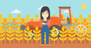 Woman standing with combine on background. An asian female farmer standing on the background of combine harvesting wheat. Young farmer working on a wheat field Stock Photos