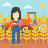 Woman standing with combine on background. An asian female farmer standing on the background of combine harvesting wheat. Young farmer working on a wheat field Royalty Free Stock Photo