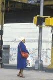 Woman standing on corner in poor neighborhood Stock Image