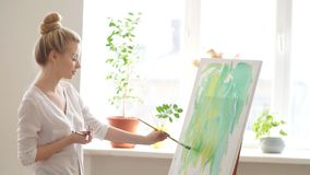 Woman standing on the corner of the room in front of the easel. Light room for painting. Woman standing on the corner of the room in front of the easel stock video