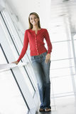 Woman standing in corridor smiling Stock Photo