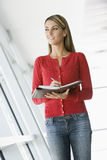 Woman standing in corridor writing in notebook Royalty Free Stock Photo