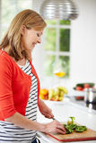 Woman Standing At Counter Preparing Meal In Kitchen Royalty Free Stock Image