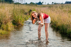 Woman standing in creek in summer Stock Photos