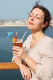 Woman standing on cruise liner with cocktail Stock Images