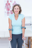 Woman standing with crutch and smiling at camera Royalty Free Stock Photography
