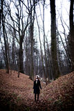 Woman standing in dark cold forest background Stock Photo