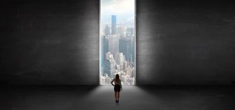 Woman looking to a cityscape from a dark empty room Royalty Free Stock Images