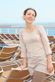Woman standing on deck of cruise ship. Beautiful woman standing on deck of cruise ship near chaise longue Stock Image