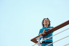 Woman is standing on deck of cruised ship Stock Image
