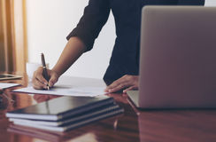 Woman standing at desk and working writing document royalty free stock images