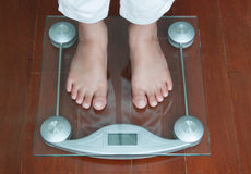 Woman Standing on Digital Weighing Apparatus,healthy. Woman Standing on Digital Weighing Apparatus Stock Photo