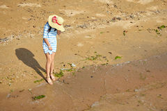 Woman standing on a dirty beach. Young woman standing on a dirty beach with algae stock photo