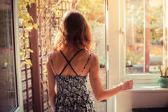 Woman standing in doorway at sunrise Stock Photography
