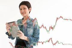 Woman standing double exposure with blur building. Trading Business woman hold smart device .and Forex Trading Lines Graphs Stock Image