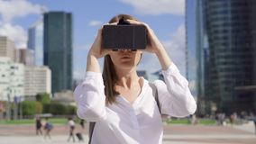 Woman standing in downtown business district using virtual reality glasses. Skyscrapers on background