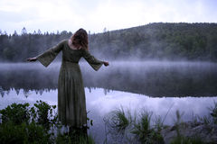 Woman standing in dress at lake Stock Images