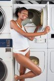 Woman Standing By Dryer In Laundry Stock Images