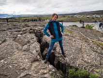 Woman is standing on an earth gap at Thingvellir National Park -. Attractive woman is standing on an earth gap at Thingvellir National Park - Iceland Stock Photos