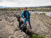 Woman is standing on an earth gap at Thingvellir National Park -. Attractive woman is standing on an earth gap at Thingvellir National Park - Iceland Stock Images