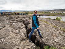 Woman is standing on an earth gap at Thingvellir National Park -. Attractive woman is standing on an earth gap at Thingvellir National Park - Iceland Royalty Free Stock Image