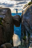 A woman is standing on the edge of a boulder Kjeragbolten stuc. K in between the mountain crevices of Kjerag above a fjord, near Lysebotn, Norway. The feeling of Stock Photo