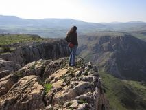 Woman standing on edge of a cliff stock photos