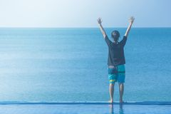 Woman standing on edge of swimming pool with raised hands over head, she looking at seascape view. stock photos
