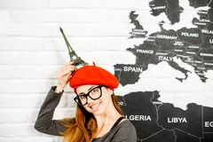 Woman dreaming about a trip to Paris. Woman standing with eiffel tower near the wall with world map on the background, dreaming about a trip to Paris Royalty Free Stock Photos