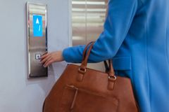 Woman Standing In Elevator And Pressing Button royalty free stock photography