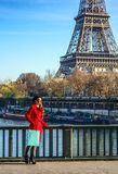 Woman standing on embankment near Eiffel tower in Paris, France Royalty Free Stock Photography
