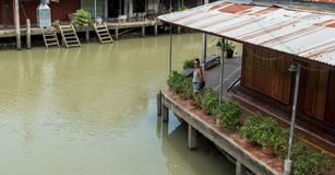 Woman standing on empty dock at floating market stock image