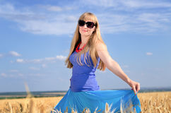 Woman standing enjoying the sun in a wheat field Stock Image