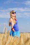 Woman standing enjoying the sun in a wheat field Stock Photos