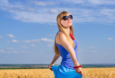 Woman standing enjoying the sun in a wheat field Stock Images