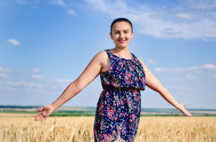Woman standing enjoying the sun in a wheat field Stock Photos